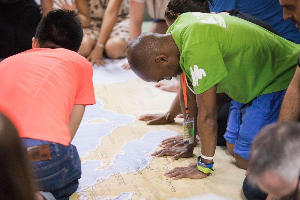 Menschen beten auf einer auf dem Boden ausgebreiteten Weltkarte