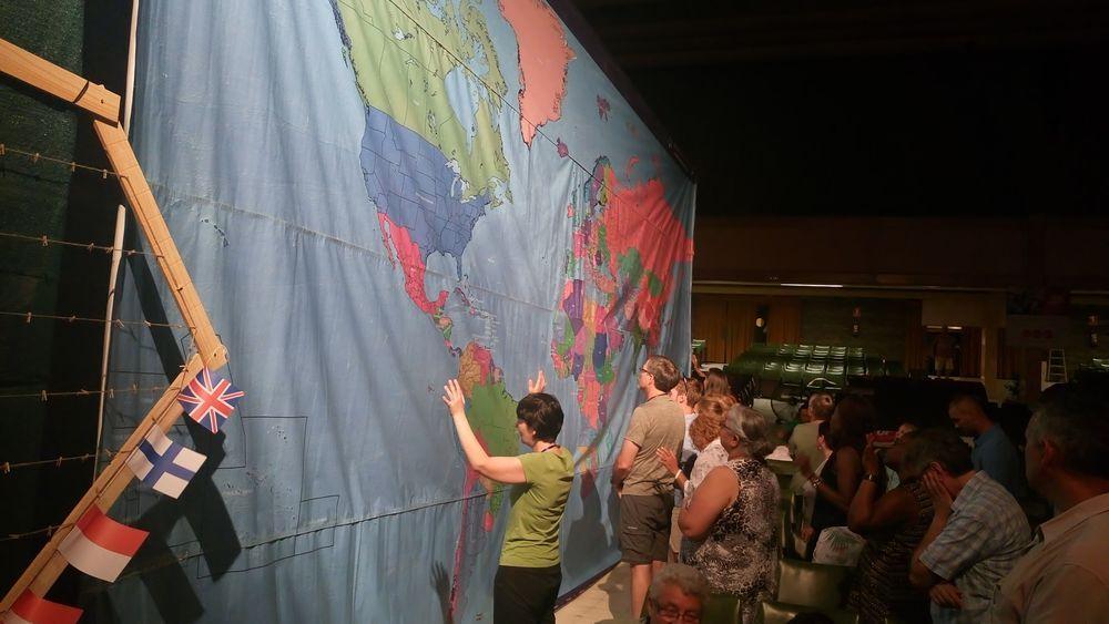 Menschen beten vor einer riesigen Weltkarte