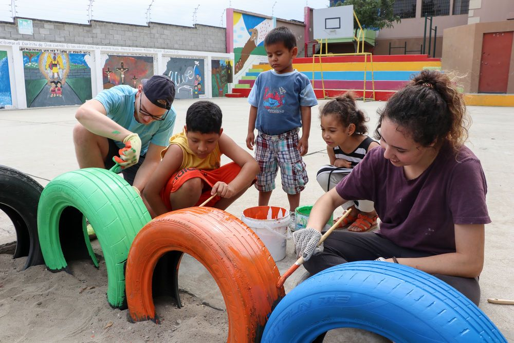 Ecuador: Manta, Ecuador :: Several children help Mateo Brink (South Africa) and Camila Winter (Argentina) paint tyres around the edge of their sandbox bright colours. More Info