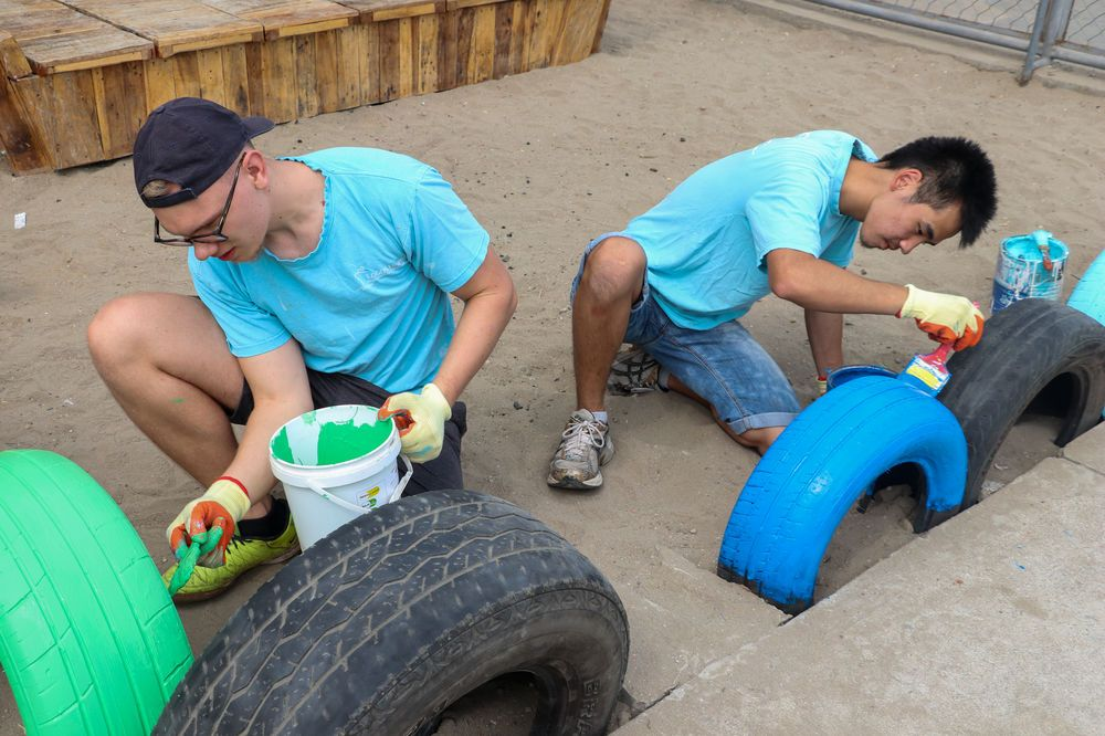 Ecuador: Manta, Ecuador :: Mateo Brink (South Africa) and Erdenebold Bold (Mongolia) help paint tyres around the edge of a sandbox bright colours. More Info