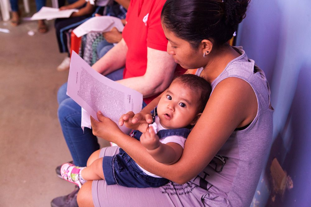Ecuador: Guayaquil, Ecuador :: A young mother reads the Fathers love letter as she holds her newborn baby. More Info