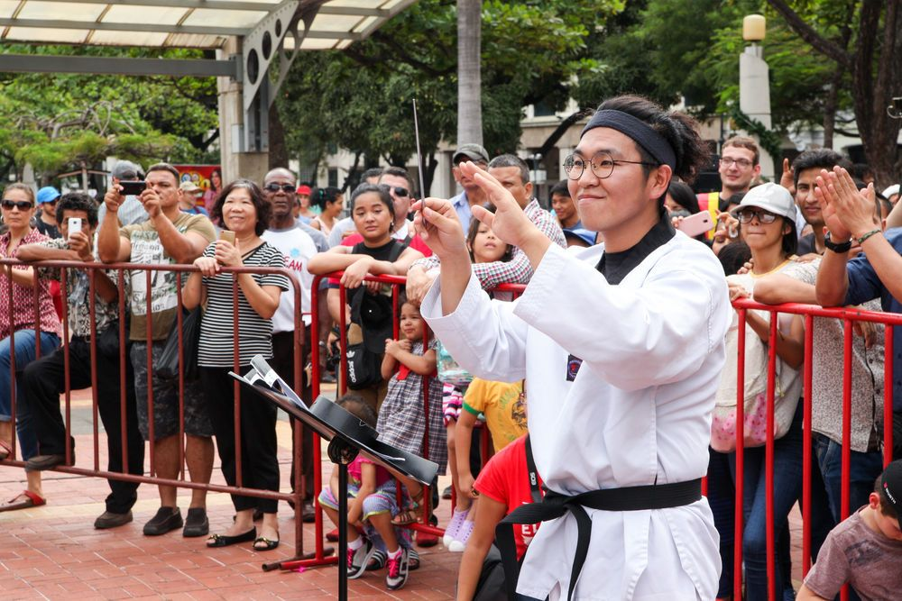 Ecuador: Guayaquil, Ecuador :: Heejo Lee (South Korea) conducts a Korean choir at an open air cultural event. More Info