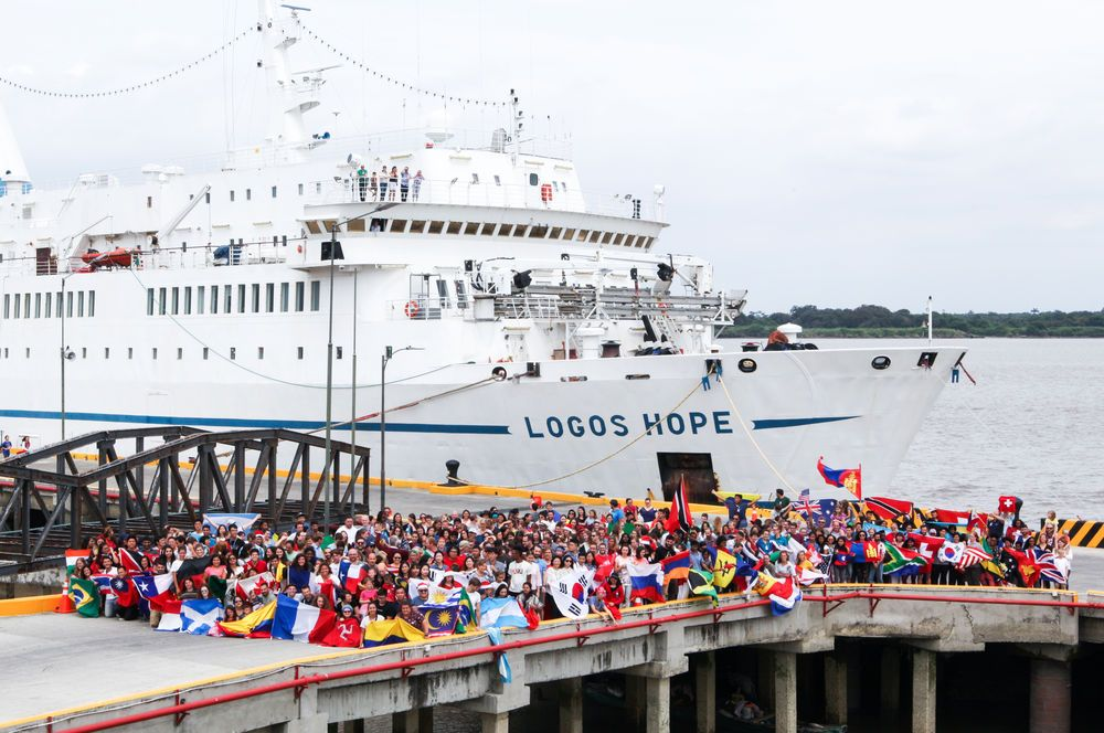 Ecuador: Guayaquil, Ecuador :: Crewmembers wave their flags on the quayside of Logos Hope. More Info