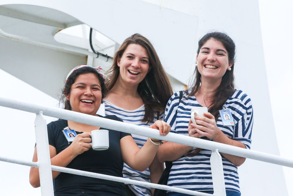 Chile: Antofagasta, Chile :: Valeria Balderas (Mexico), Roselyn Faensen- Glienke (Germany) and Camille Vonnez (Switzerland) wait outside on deck as Logos Hope arrives in port. More Info