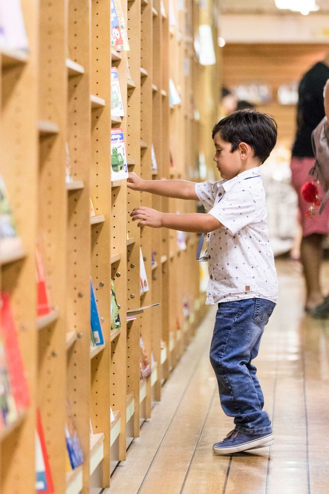 Chile: Antofagasta, Chile :: A young boy looks explores shelves of books in the bookfair on board Logos Hope. More Info