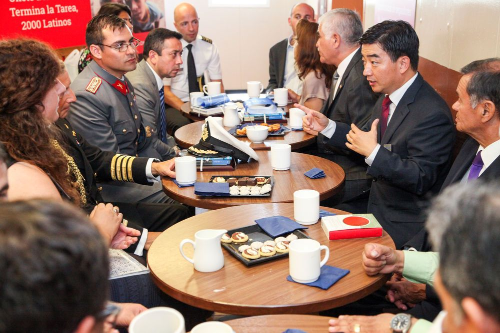 Chile: Valparaiso, Chile :: Captain Jon Helmsdal (Faroe Islands), Director Pil-Hun Park (South Korea), crewmembers and guests of honor connect after the official opening with coffee and treats in the international cafe. More Info