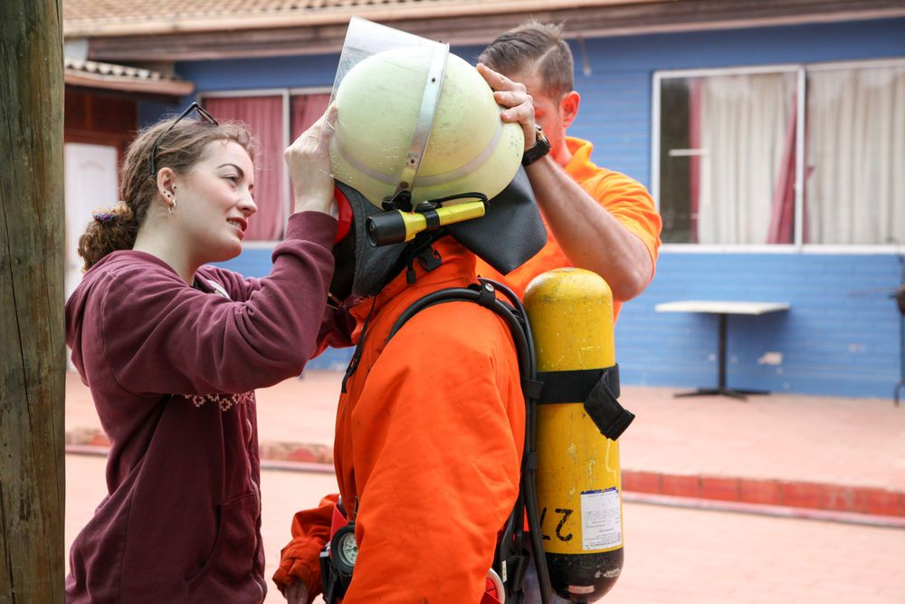 Chile: Valparaiso, Chile :: Kat Mowat (Scotland) helps a new crewmember try on fire-fighting equipment as part of their pre-ship safety training. More Info