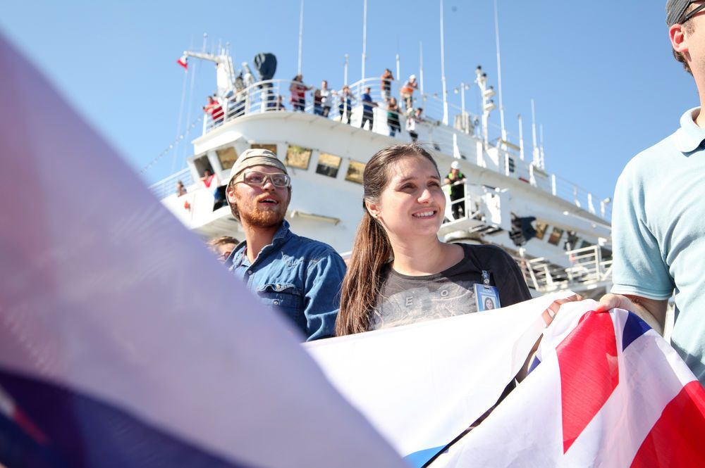 Chile: Lirquèn, Chile :: As part of the traditional flag tunnel, David Demirgian (USA) and Galina Tsirkovnaia (Russian Federation) welcome new crewmembers on board Logos Hope. More Info