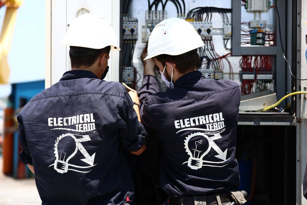 Curaçao: Willemstad, Curaçao :: Electrical team members connect the shore power supply in dry dock. More Info
