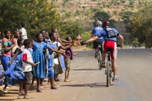 Children high five a biker during Ride 2 Transform Malawi - Rebecca Rempel