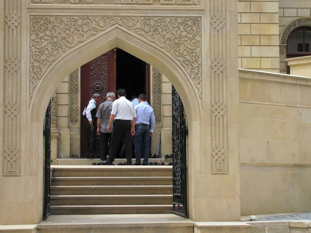 A group of men entering a mosque on Friday for midday prayers