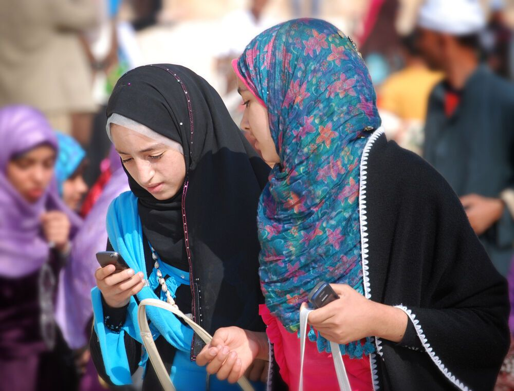 Egypt: Staying connected, two young women use mobile phones in North Africa. More Info