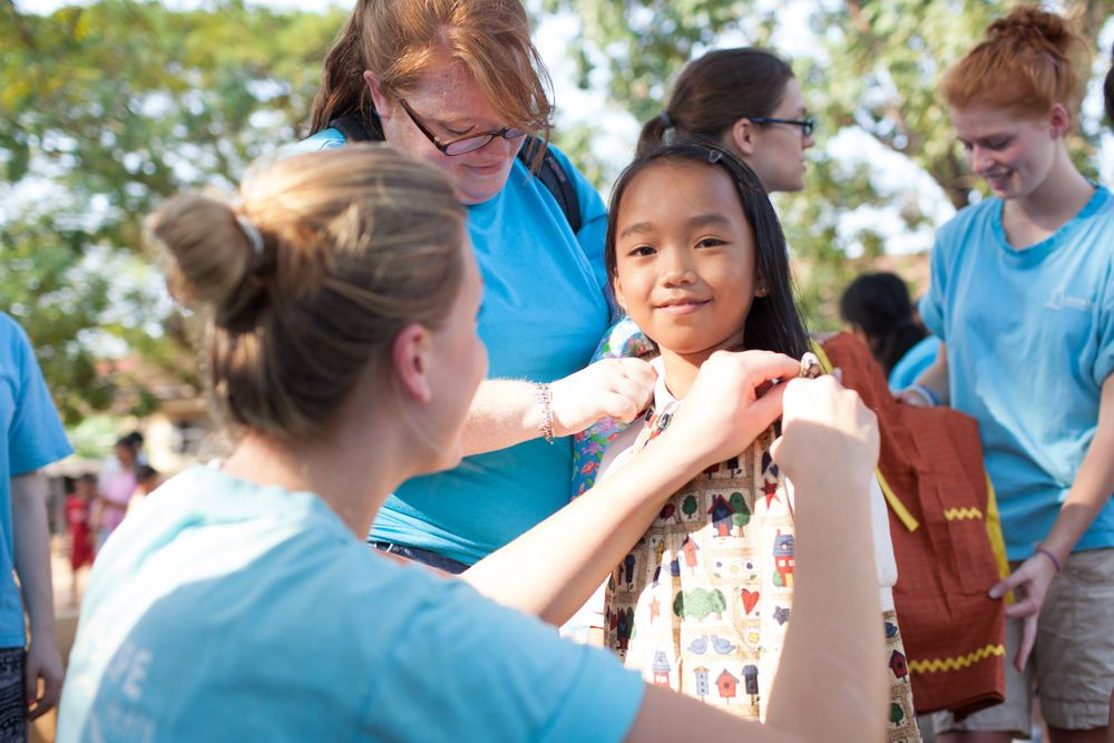 Ships: Sihanoukville, Cambodia :: Camille Papon (USA) and Juliana Grothaus (Germany) dress a local girl. The dress was donated by partner organization Dress a Girl Around the World. More Info