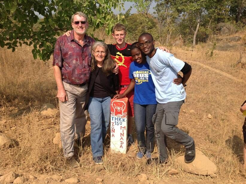OM Angola team: Wessel, Joan and Tiago van der Merwe, Marta and Nando in front of mine warning sign