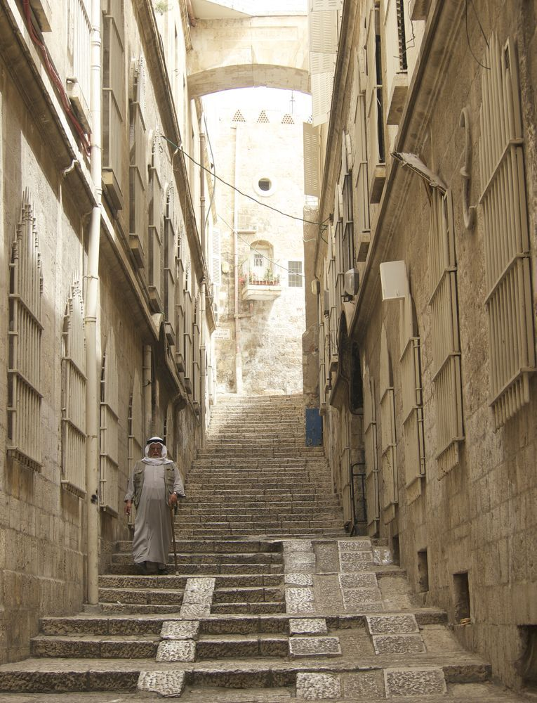 Israel: A Muslim man walks down the stairs into bustling streets in Israel.  