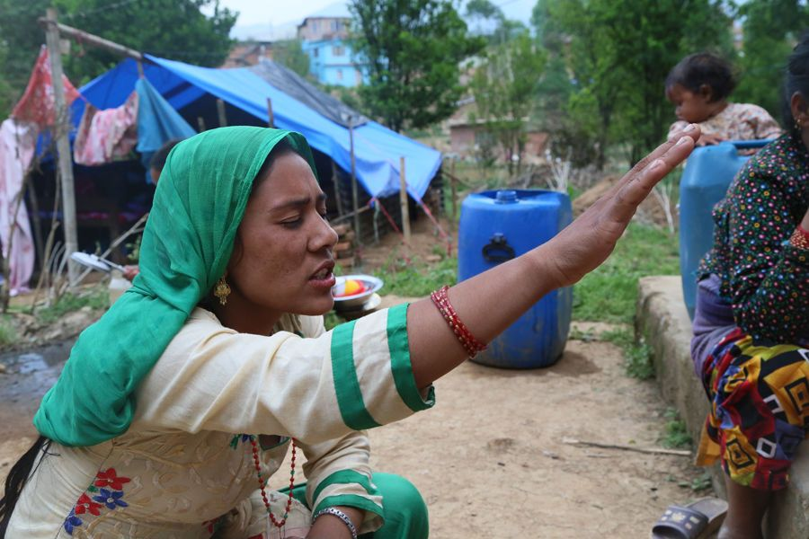 Nepal: A local Nepalese woman prays for her country with some OM Nepal team members who were visiting her near the tent where she has been living after her house was damaged in the 25th April earthquake. More Info