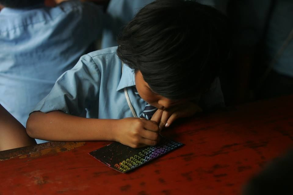 Nepal: A young girl uses magic paper during an arts and crafts lesson at OM Nepals kids trauma counselling camp.  More Info