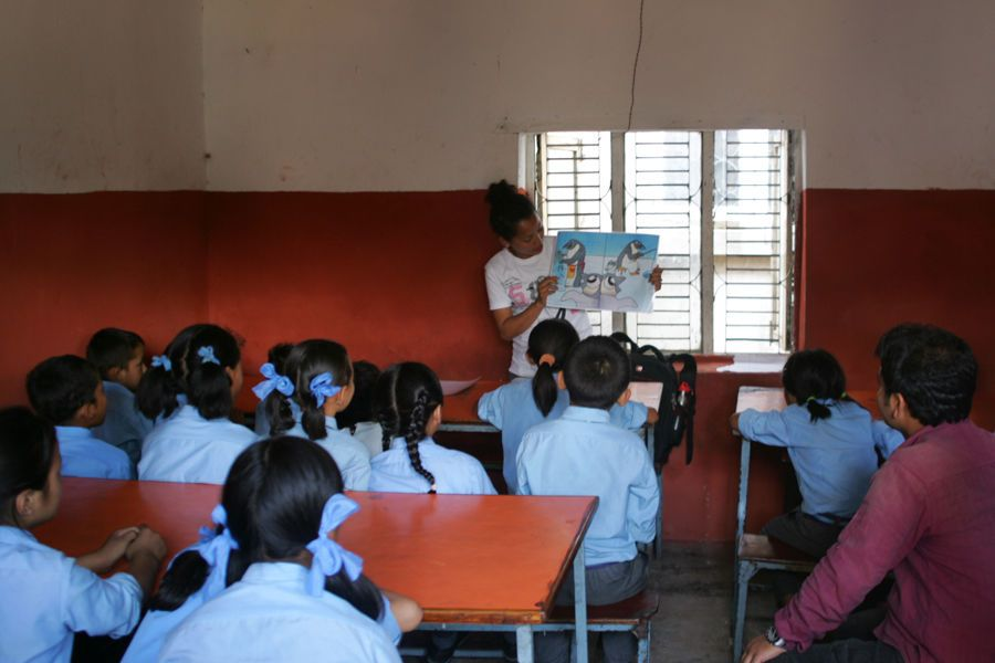 Nepal: A volunteer leader teaches a young group of students about the days theme You are not alone using a book about a penguin to narrate it. More Info