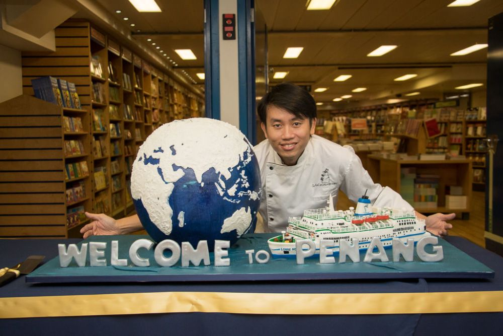 Ships: Penang, Malaysia :: Swens Wong and the cake he designed and created as a donation to Logos Hope for the onboard event Official Opening. More Info