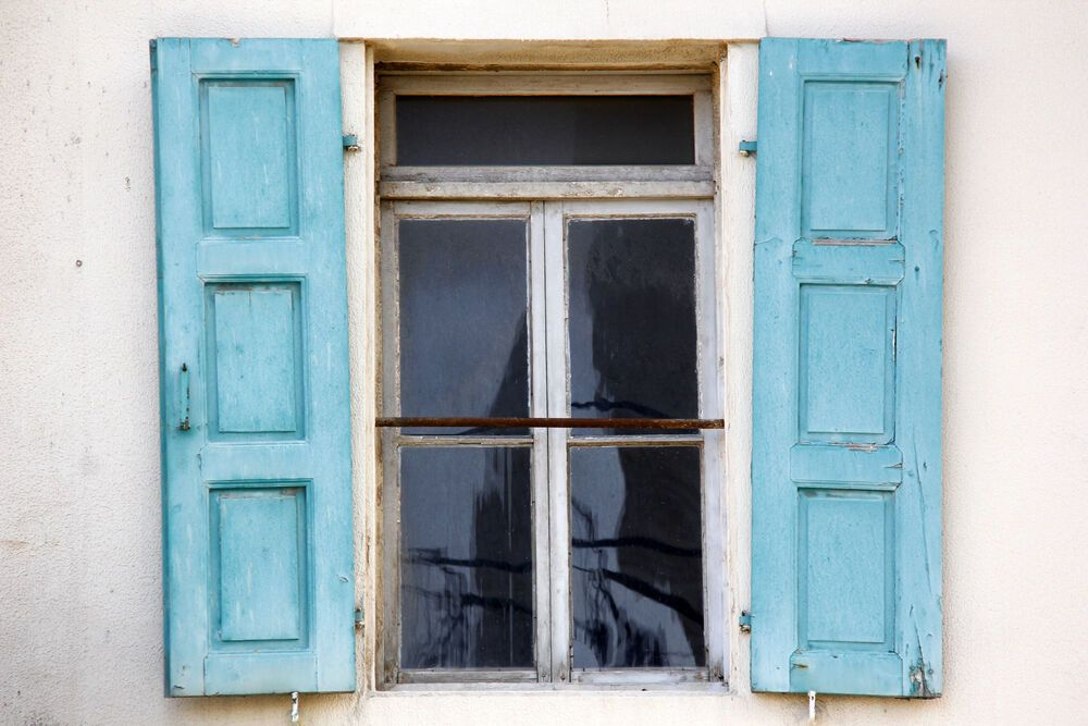 Near East: Photographer Anja Bänninger captures the essence of the window of opportunity through this artistic image of a window with traditional blue wood shutters in a village in the Near East.  Photo by Anja Bänninger More Info