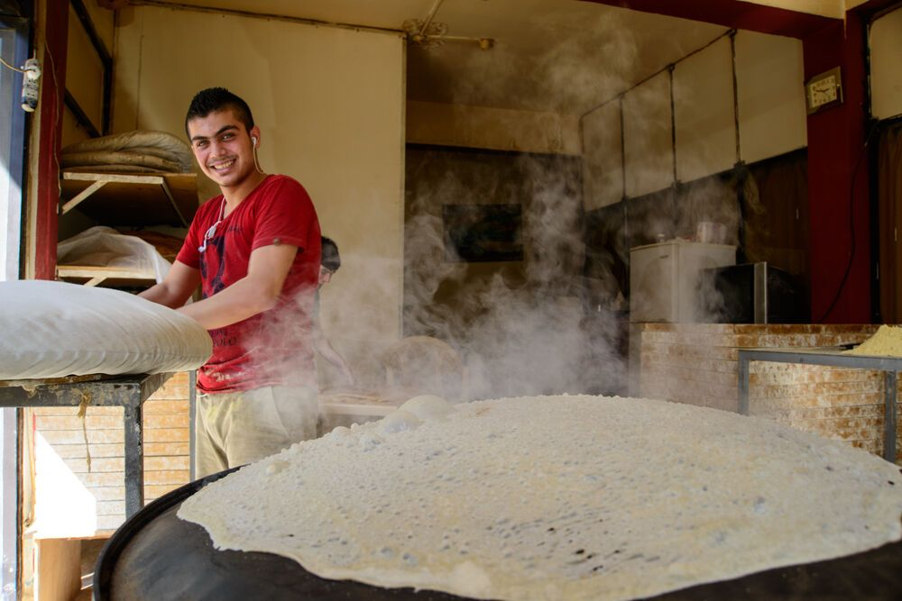 Near East: Local bread makers cook the thin Arabic bread in a side street shop.  Photo by Garrett Nasrallah More Info