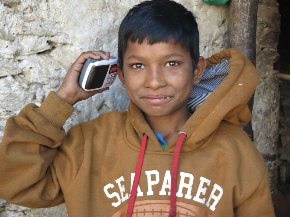 International: A young boy uses a mini-SD card with the New Testament in his radio to listen to the book of Matthew for the first time in Mugu, Nepal.   More Info