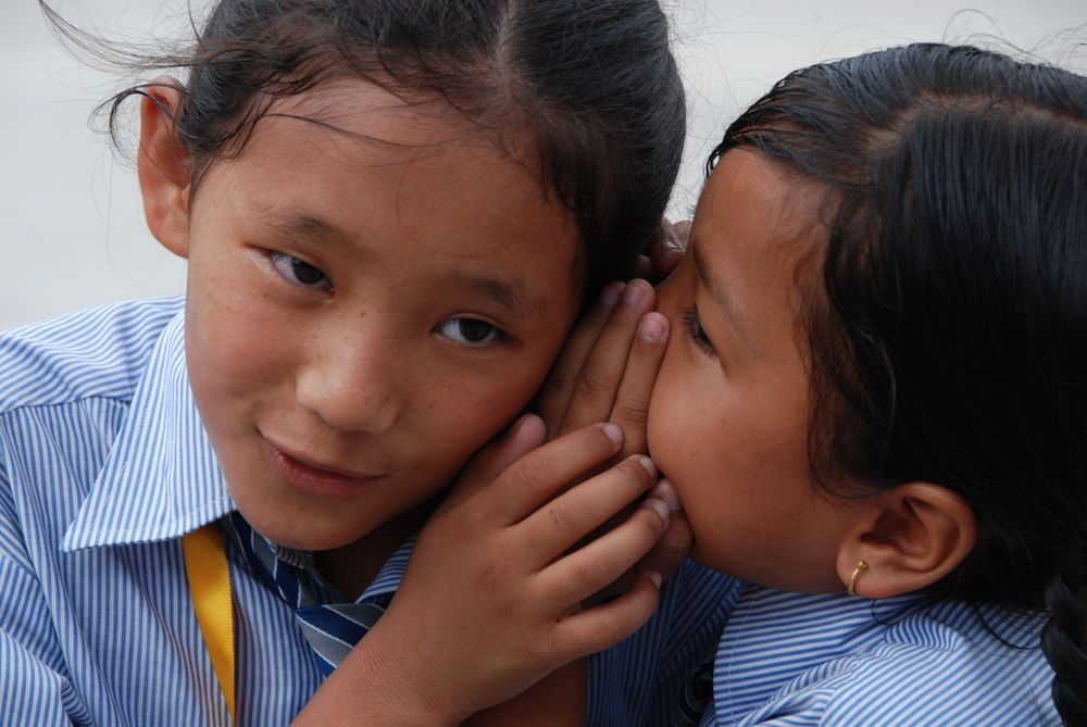 South Asia: Two school girls in Asia whisper to each other during a game activity organized by an OM team. More Info