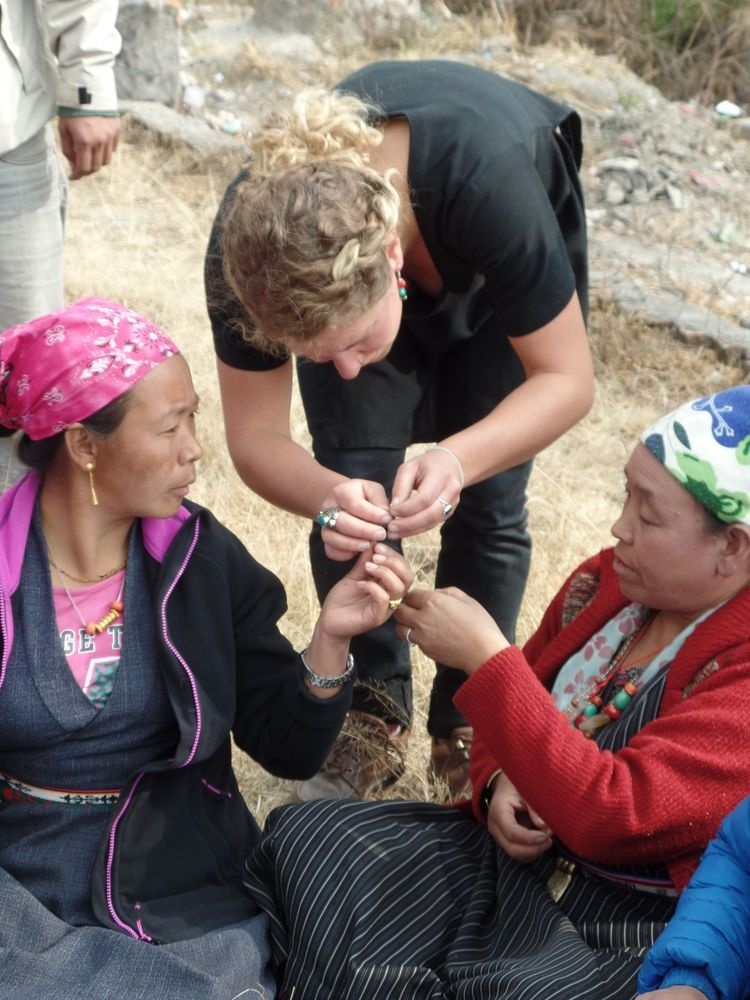 Nepal: A trainer shows some Tibetan women from Langtang how to make jewellery that they can sell to help cover costs of rebuilding their homes destroyed by the earthquake. More Info
