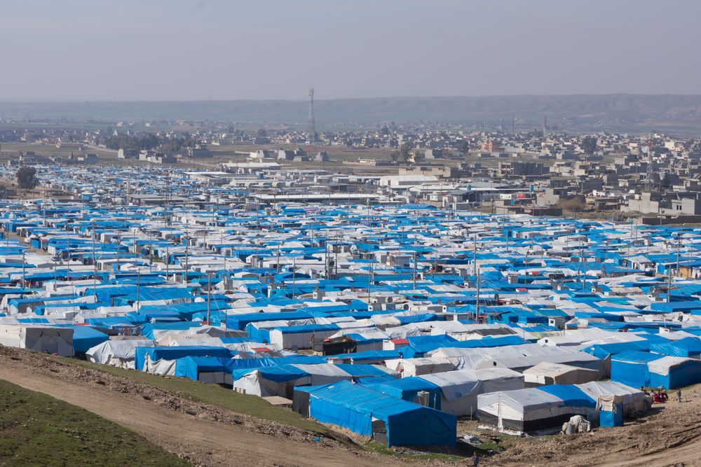 Near East: Temporary camp for refugees and Internally Displaced Peoples (IDPs) fills the valley with white tents and blue tarps.  