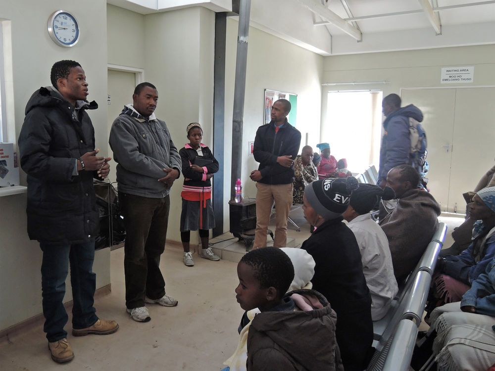 Ships: Mokhotlong, Lesotho :: Kapela Sibiya (South Africa - left) speaks with locals waiting at a clinic. More Info