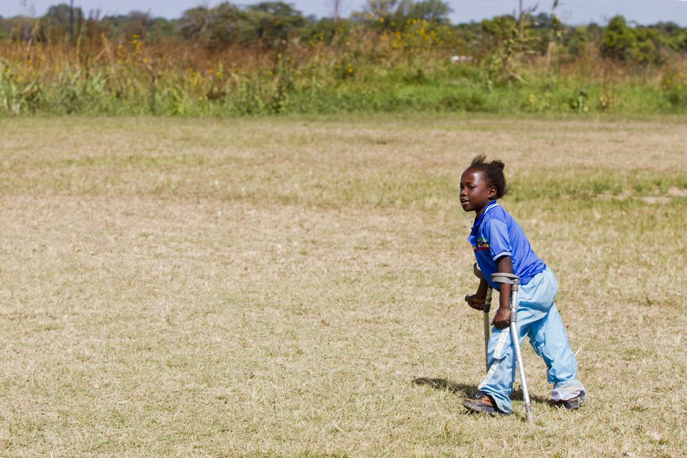 Zambia: With the aid of crutches and leg splints provided by Bethesda Mercy Ministries, nine-year-old Yande walks across a field. More Info