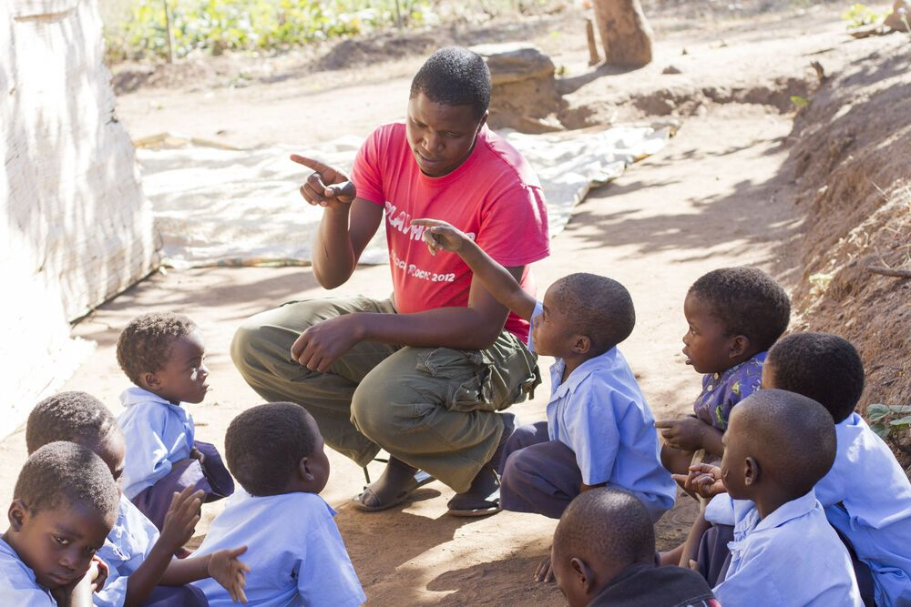 Lovedale, Zambia, teaches his class to write the letter c in the dirt outside Mbweni School in Chisopi, Malawi