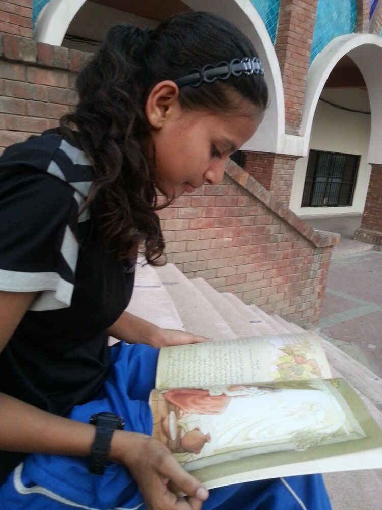 Pakistan: A young athlete reads a storybook. More Info