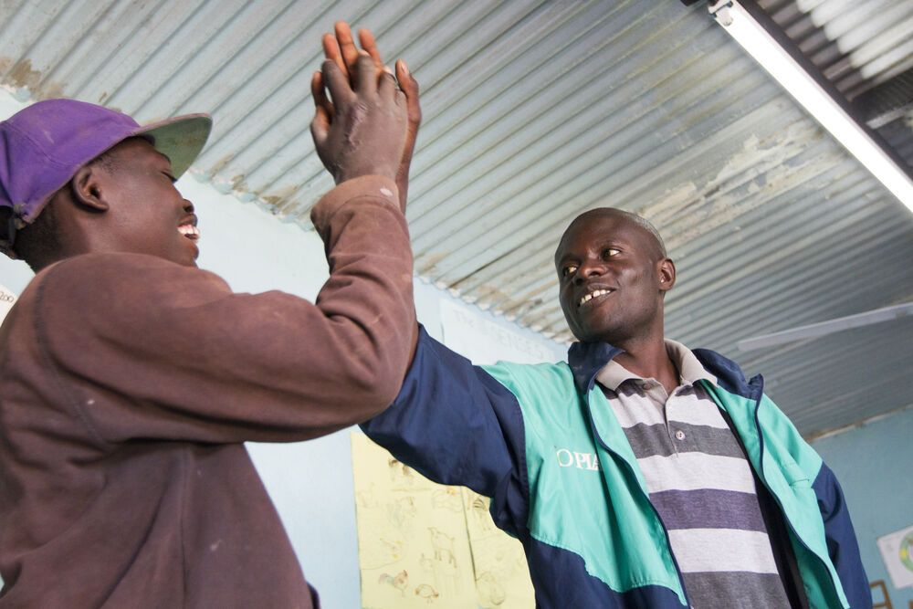 Zambia: Teacher Sydney congratulates a student at Mercy House on getting a question right. More Info
