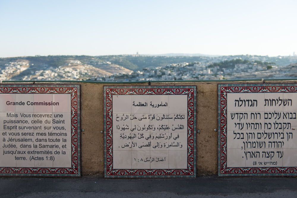 Israel: The Great Commission in Acts 1:8, written in many languages, including Arabic and Hebrew, sits above the city of Jerusalem. More Info