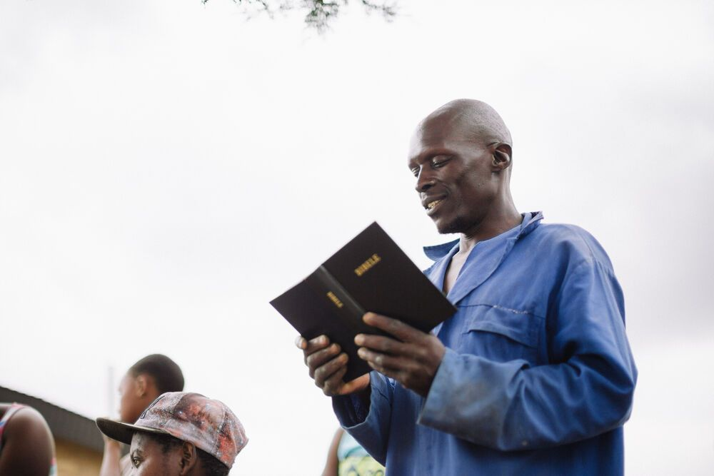 A Lesotho man reads publically from the Bible.