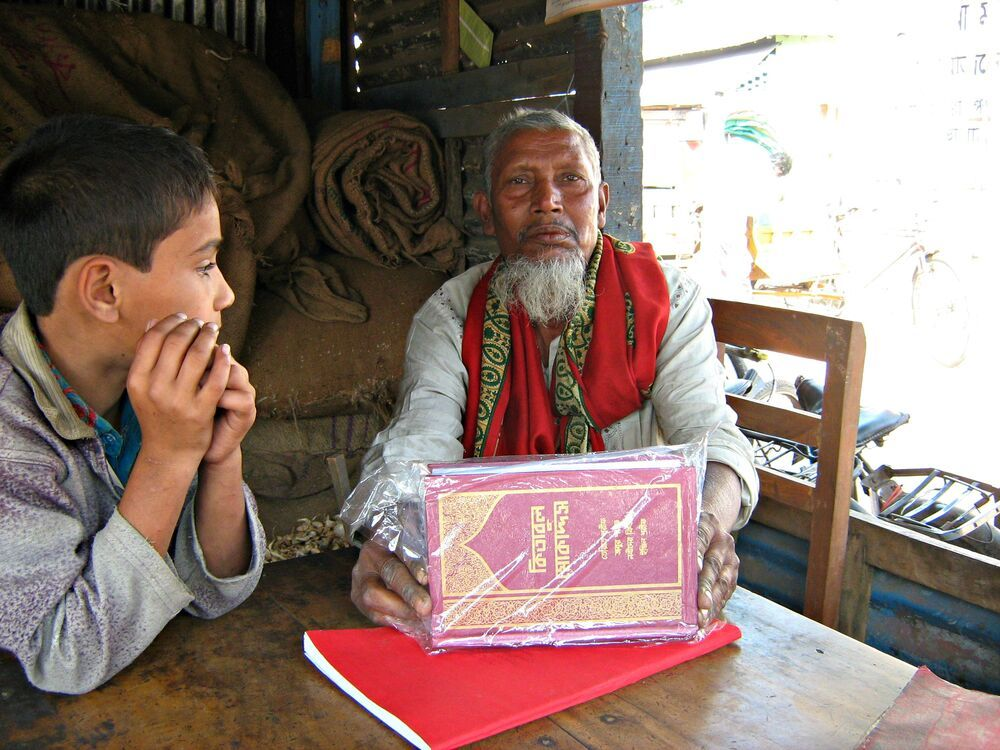 Bangladesh: An elderly man in a Bangladesh shop with a Bengali Bible he bought. Throughout Bangladesh Gods Word is reaching people who have never heard about Jesus. More Info