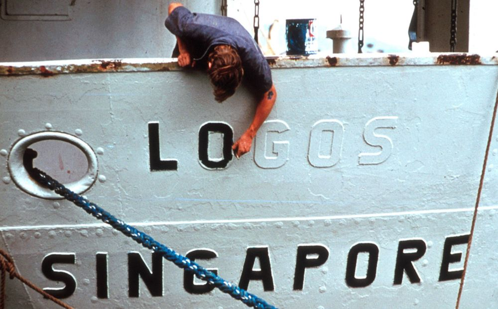Painting the name Logos on the first OM ship after her purchase.
