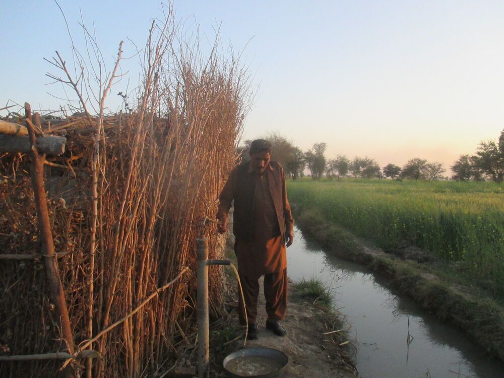 Pakistan: A man taking water from a hand pump More Info
