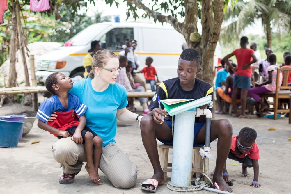 Ghana: Sekondi, Ghana :: Antonia Kinas (Germany) holds a boy with cerebral palsy while she encourages a teen as he completes his homework during Logos Hopes visit to Fathers Home orphanage. More Info