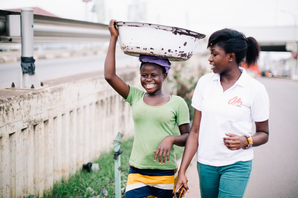Ghana: Portia, an OMer from Ghana, walking with one of the Kayeye ladies that she ministers to. More Info