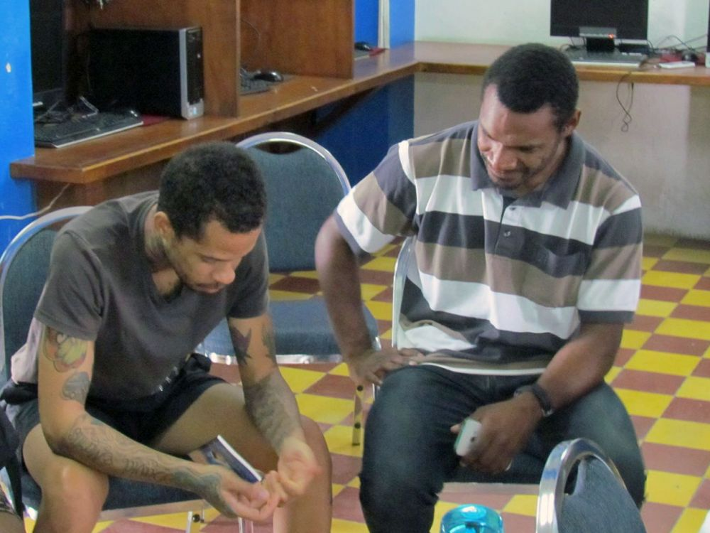 Curaçao: Willemstad, Curaçao :: Ofasia Wayne (Papua New Guinea, on right) shares Gods love by explaining the Scripture behind a young mans tattoos. More Info
