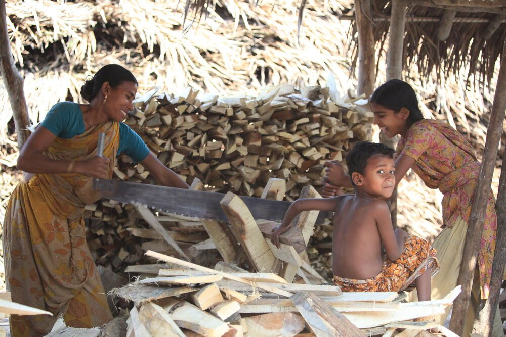 Bangladesh: A mother and daughter share a smile while working together in the woodyard. More Info