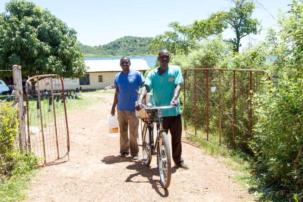 OMers Kaunda, left, and Alex load nshima and water onto a bike to take to the local prison. Three times a week OM Lake Tanganyika team members visit the prison to share the Word of God and provide a meal for the prisoners.