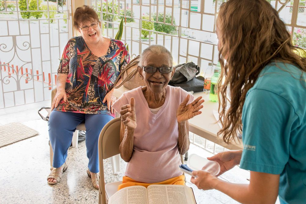 Jamaica: Kingston, Jamaica :: An elderly lady in a care home is overjoyed to be able to read her Bible with her new glasses, provided by crewmembers from Logos Hope. More Info