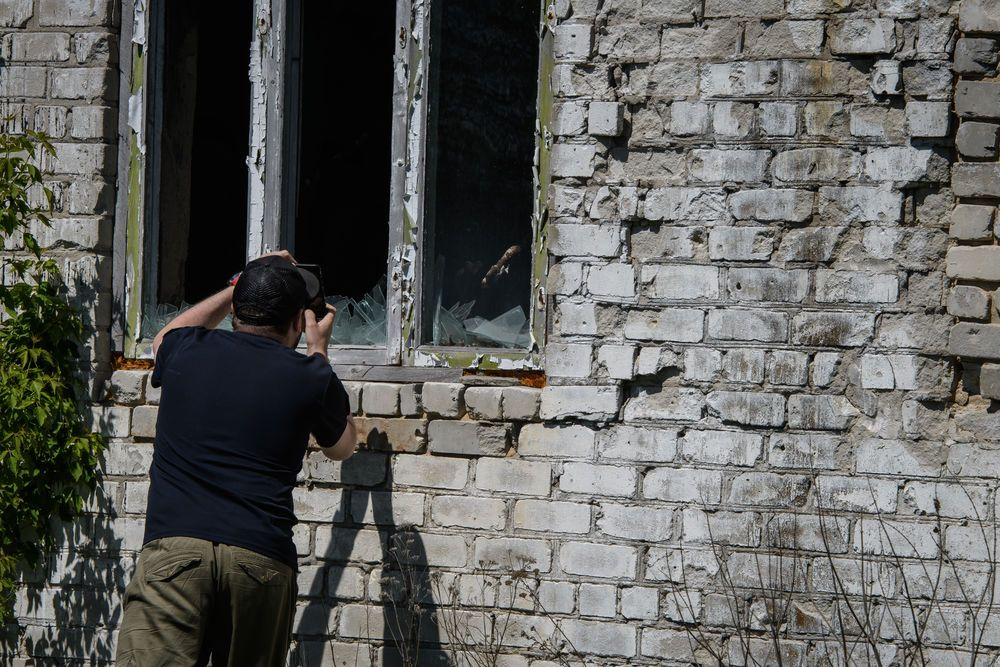 A Ukrainian man take a picture with his phone of the destruction caused by war within the conflict zone of eastern Ukraine.  Photo by Garrett N