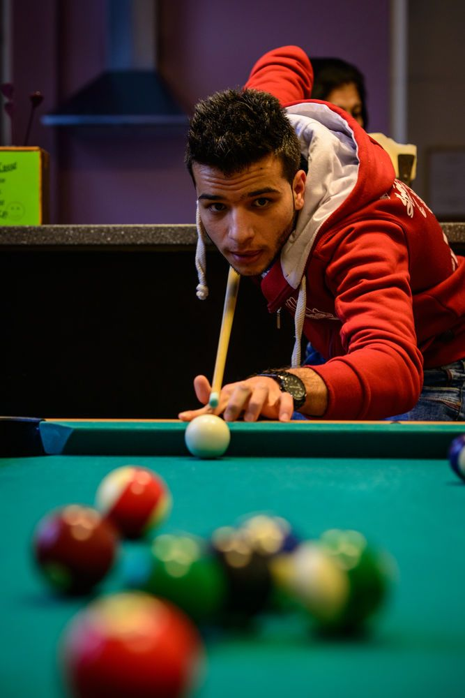Syria: Young refugee boys play pool during Xenos teams weekly coffee social; this is a great way to break down walls and loosen conversation.   Photo by Garrett N More Info