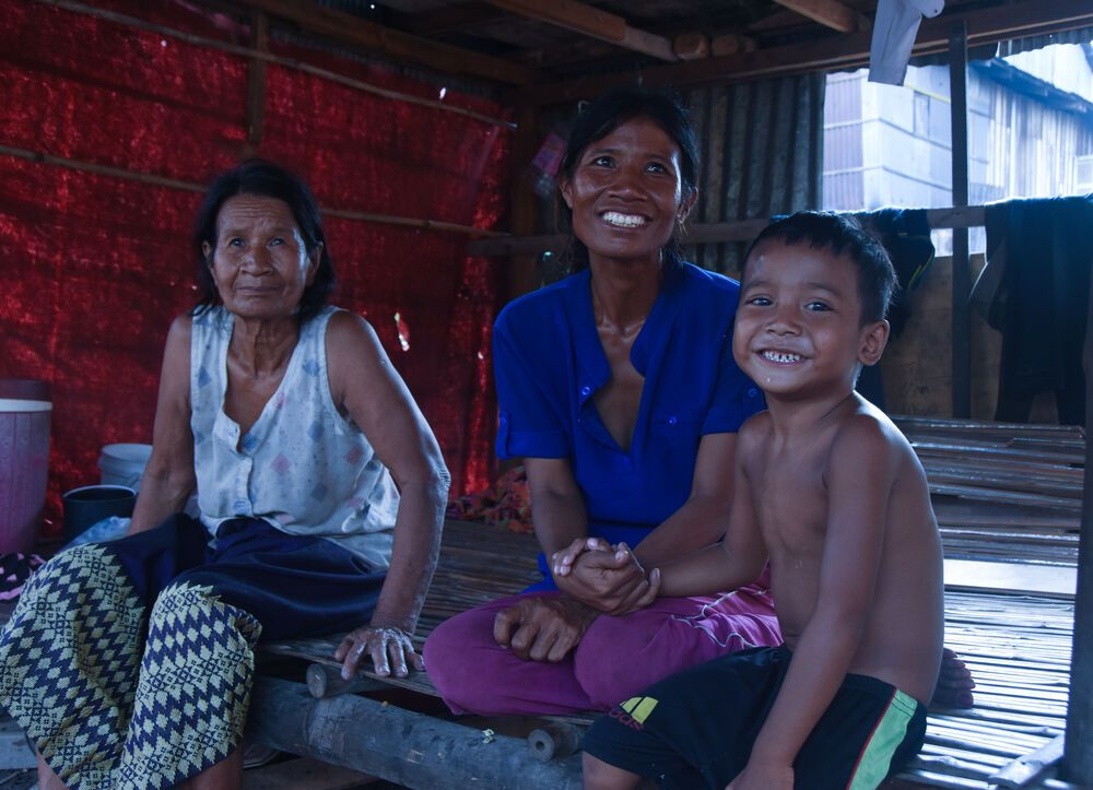 Cambodia: A young boy and his mother and grandmother sit in the kitchen area below their bamboo and tin home, that MTI Cambodia built for them. More Info
