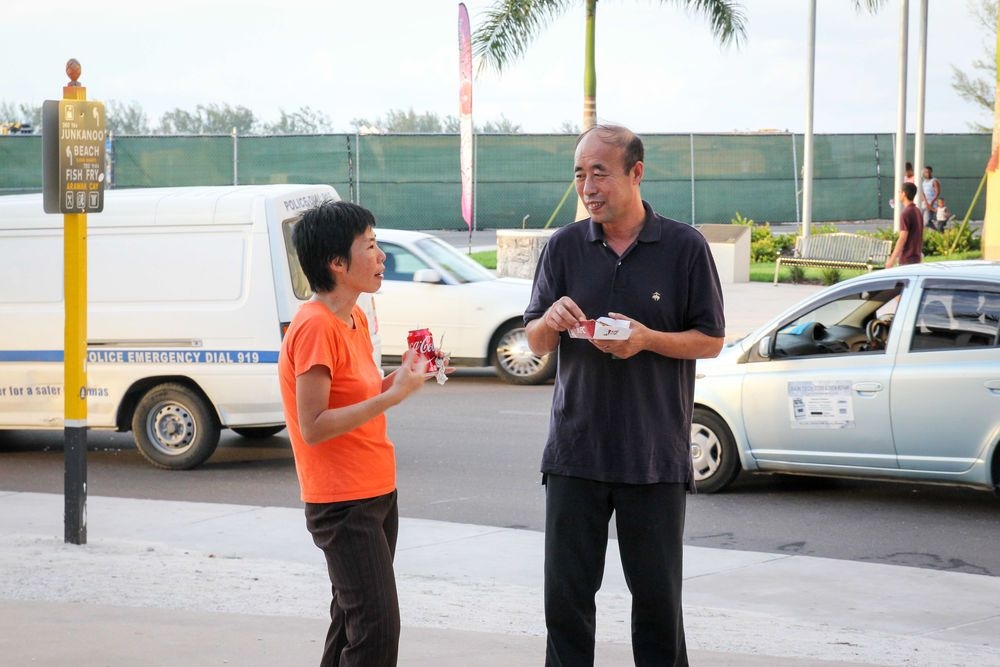 Bahamas: Nassau, The Bahamas :: Wan Li Haw (Malaysia) talks with a man in her mother-tongue while connecting with people on the street. More Info