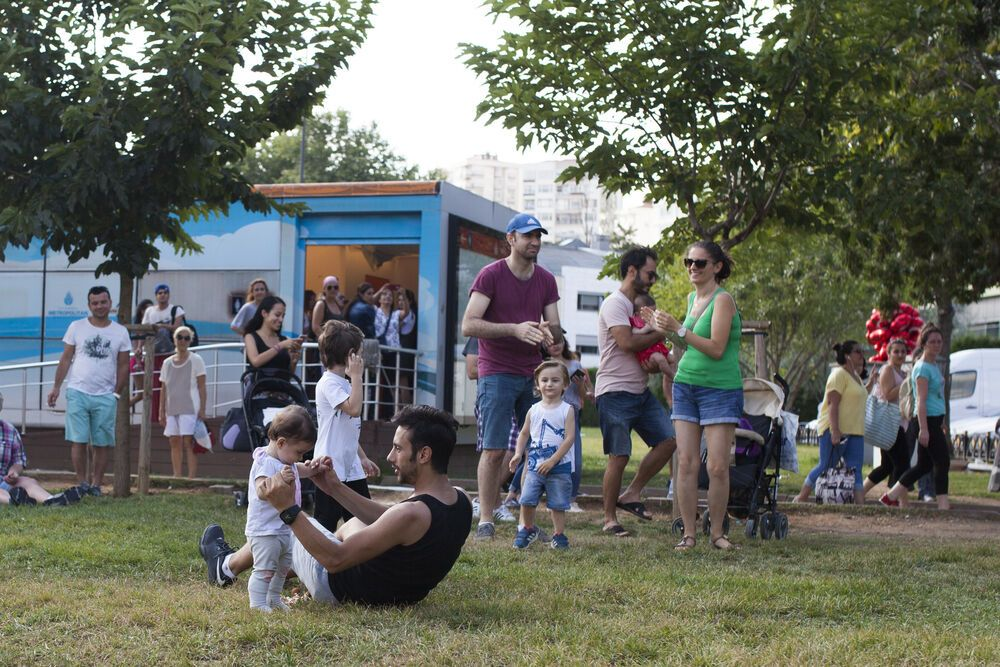Turkey: A man dances with his daughter as an audience gathers to watch the TACO team perform music in a local park. More Info